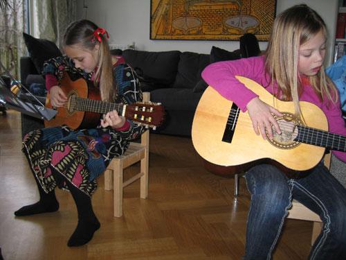 Isa en Myrthe oefenen na hun eerste gitaarles